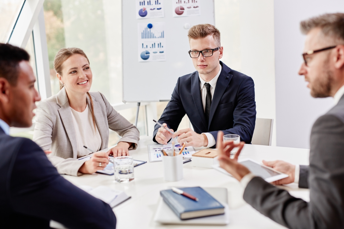 Group of confident colleagues interacting at meeting in office